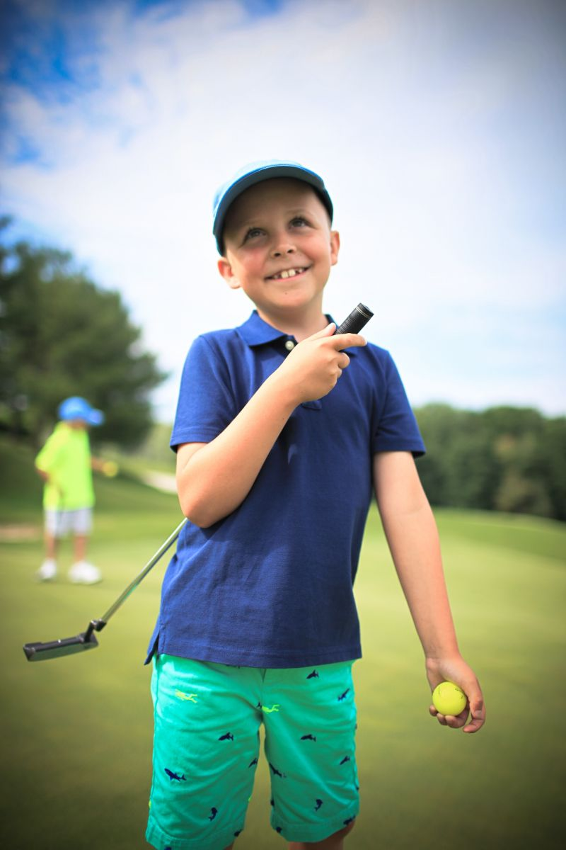 A young boy smiles with a club and a golf ball