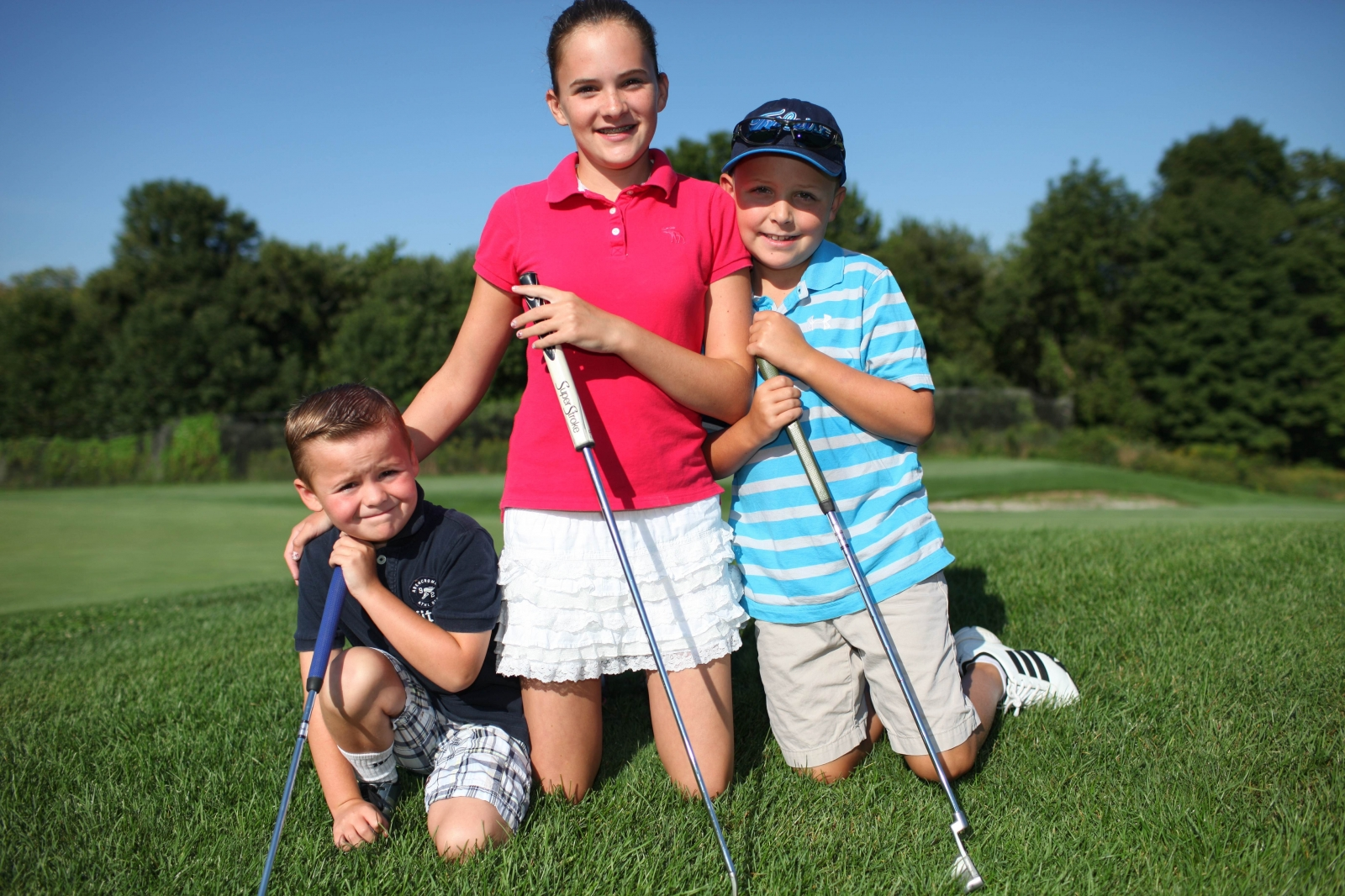 Three kids pose with their golf clubs at Centennial Golf Club in Carmel, NY